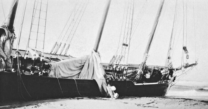 The hull of a grounded schooner lying at an angle on the beach, with most masts and rigging still intact, and a tumble of sail and rope hanging over the side.