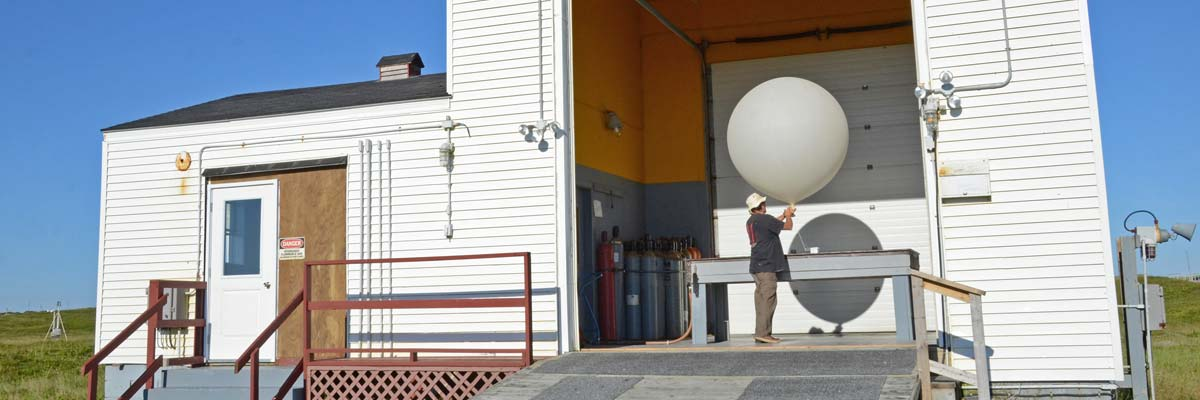 With the large, roll-back door open and sunshine flooding into the high-ceilinged room, a man holds a large white balloon. The round balloon is about 1.5 m wide and is filled with hydrogen gas.